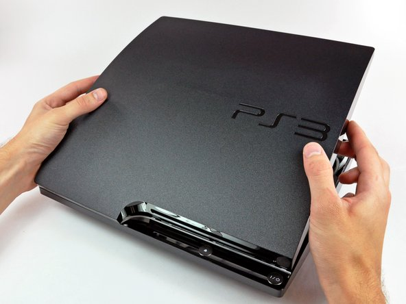 Image 1/2: Lift the top cover off the PS3.
