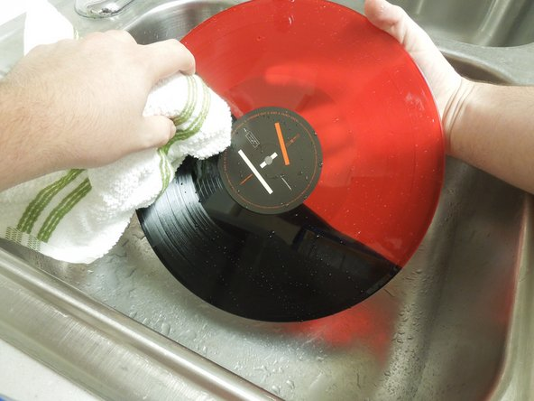 Take a dry lint-free cloth and dry the LP record in a circular motion until wet spots are visibly gone.