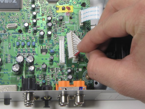 Remove the first of two ribbon cables connected to the Left-Side Motherboard (Green) by pulling vertically.