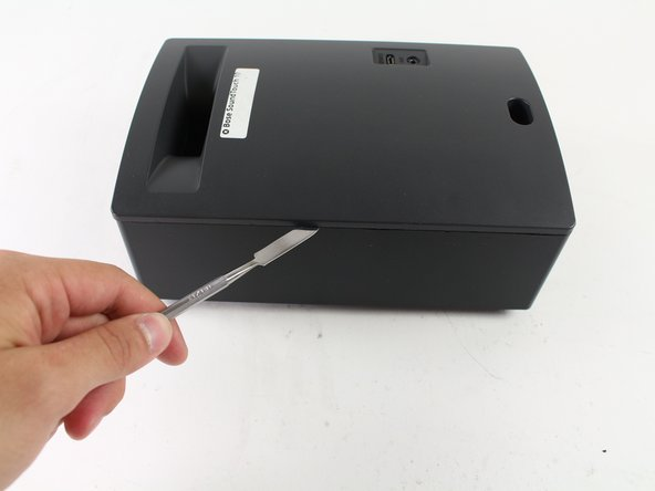Image 1/1: Loosen the adhesive by sliding a Metal Spudger under the edge where the back panel meets the speaker's body.