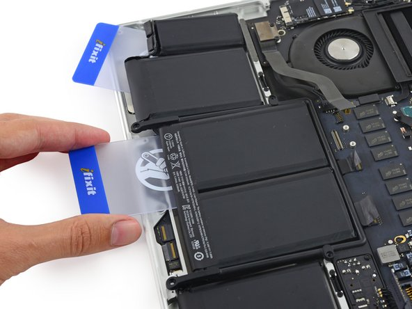 It may help to elevate one side of your MacBook Pro a few inches so that the adhesive remover flows in the correct direction, underneath the battery cells. You can use a sturdy book or foam block to prop up one side of your MacBook Pro while you work.
