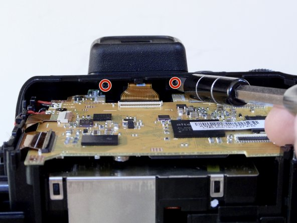 Remove the two 4 mm screws with a Phillips 000 screwdriver under the viewfinder.