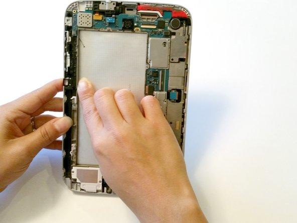 Drehe das Tablet herum und drücke ganz vorsichtig das LCD von der Rückseite, aber nur an der Kante mit dem Anschaltknopf. Drücke vorsichtig durch die Öffnung für den Akku.