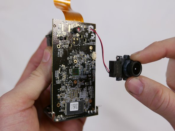 Using your forefinger and thumb, grip the top and bottom of the lens assembly and pull away from the motherboard.