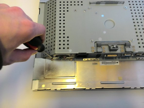 Now we need to start detaching the electronics from the screen.  The first step for this is to remove the plates protecting the wires.  There are a total of 5 screws holding two plates onto the top and bottom.
