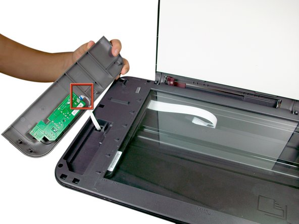 Image 2/2: Disconnect the ribbon by pinching the blue tab and pulling away from the green circuit board.
