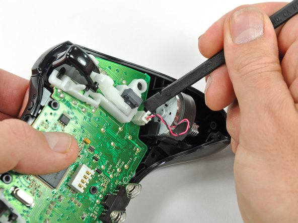 Use the flat end of a spudger to remove the vibration motor cable, moving it upward from its socket on the logic board.