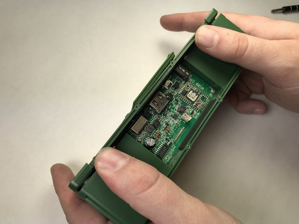 Turn the device around and remove the rear panel from the device to reveal the device's speaker units.