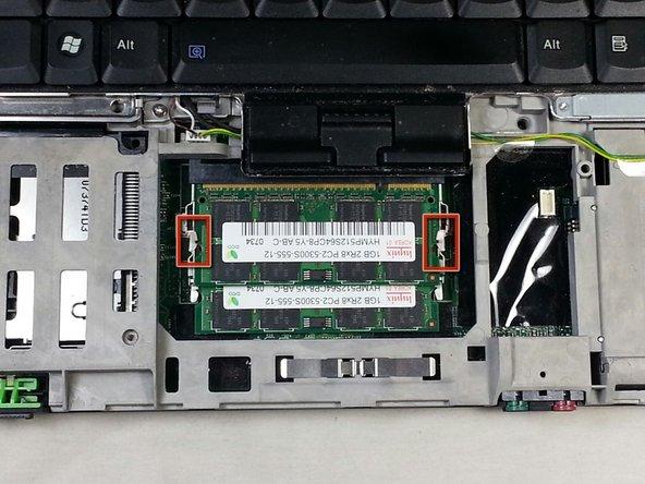 Écartez les deux languettes en même temps sur le côté de la barrette de RAM.