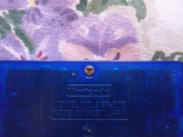 Use a Y1 screw driver to remove the screw on the back of the game cartridge.