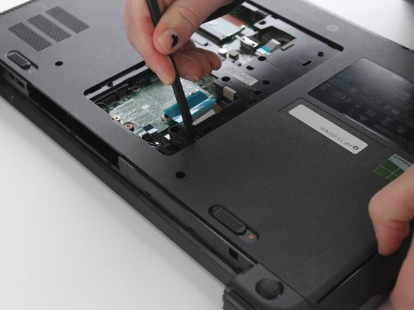 Push down the tab that is located by the DVD drive screw.