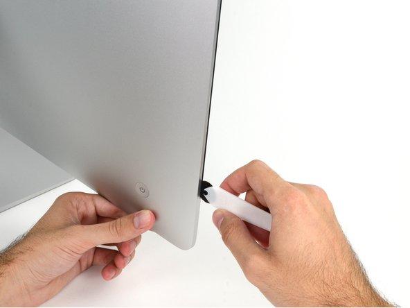 Beginne an der linken Seite des Bildschirms, auf der Seite der Ein-/Aus-Taste, und schiebe das iMac Opening Tool zwischen Bildschirm und Gehäuse.