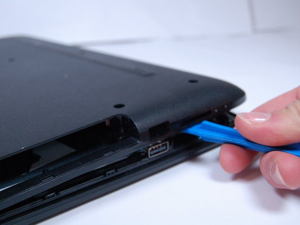 Use a plastic prod to pry the back cover off the laptop.