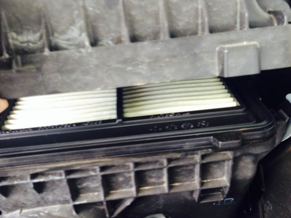 Gently lift the cover of the box from the lower part of the box.  Remove the old air filter from the box and set it aside.  Place the new air filter in the box.  Replace the cover and place the four clips back on the box.