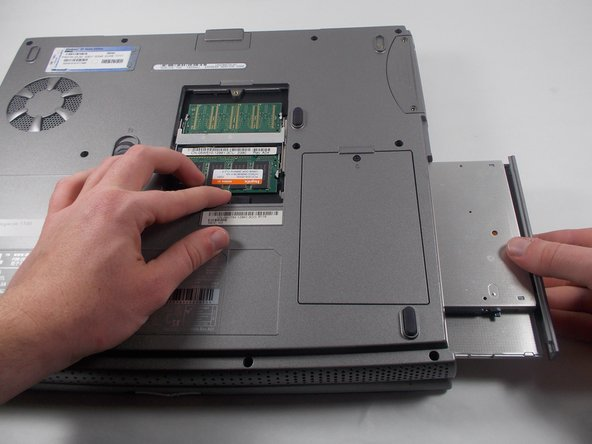 While holding down the switch in the RAM compartment, pull out the CD Drive.