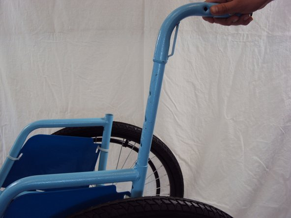 Slide each handle into the respective slot on the top of the wheelchair.