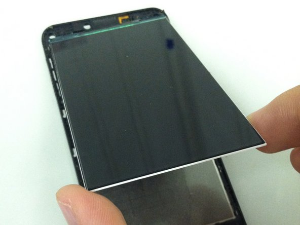 Lift the LCD from its bottom edge and work the ribbon cable carefully through the hole