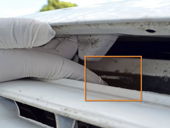 Image 2/3: Place the hood prop rod into the hole located at the front of the hood on the passenger side.