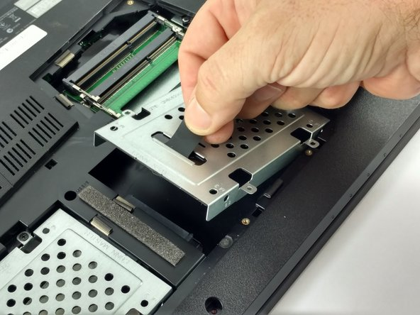 Image 3/3: Use the pull-tab to lift the hard drive housing and pull the hard drive away from the connector.