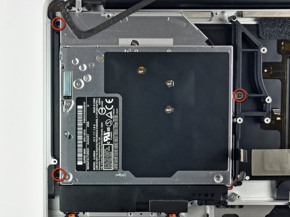 Image 1/2: Lift the optical drive from its left edge and pull it out of the computer.
