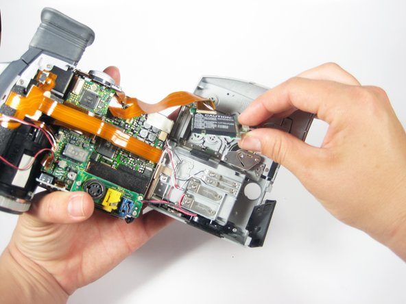 "Remove the circuit board you just unscrewed. It is the black rectangle that says ""CAUTION"" on it."