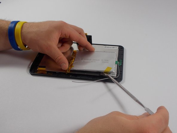 Using a metal spudger, carefully pry the battery away from the digitizer.
