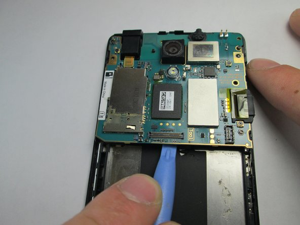Image 3/3: Use the plastic opening tool to pry the motherboard out of the phone shell.