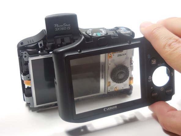 Image 2/2: Continue to pull the back panel until it completely detaches from the camera.