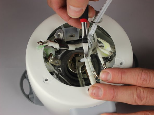 Using a pair of scissors , cut the zip tie that holds the thick power supply wire to a smaller wire.
