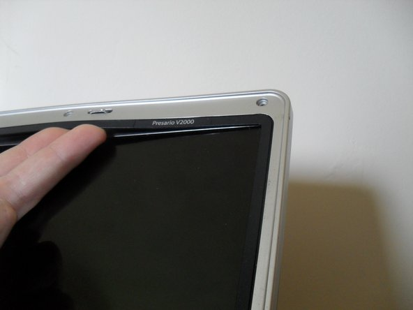 Image 1/3: Use your fingers to pry off the bezel at the top and sides first
