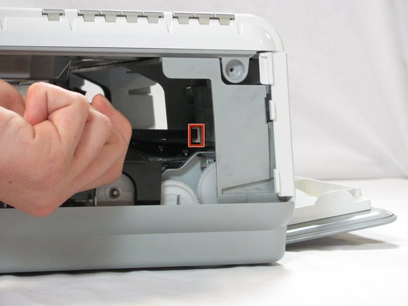 Image 1/2: Inside the printer is a small white tab. Press it inward with a spudger until a pop is heard.