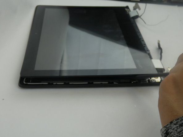 Use the black nylon spudger to lift and separate the screen from the plastic back cover.