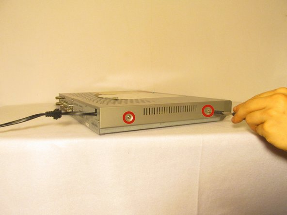 Remove the five 1cm screws on the back of the DVD player with the Phillips #1 screwdriver.