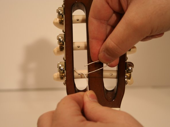 Insert the springy end of the string into the hole in the tuning peg.