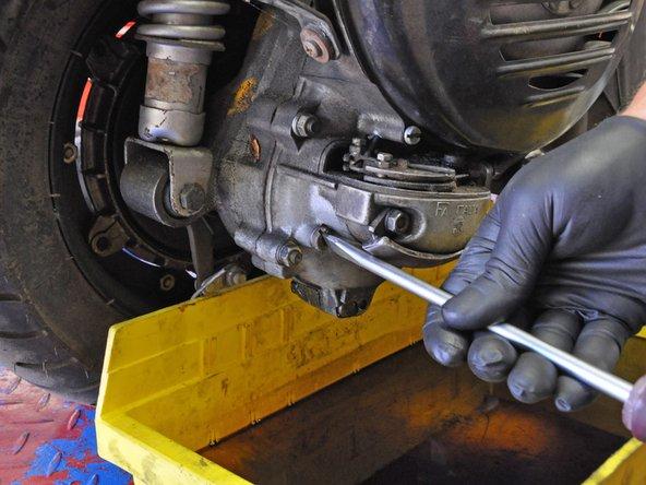 Use a large flathead screwdriver to remove the oil fill plug.