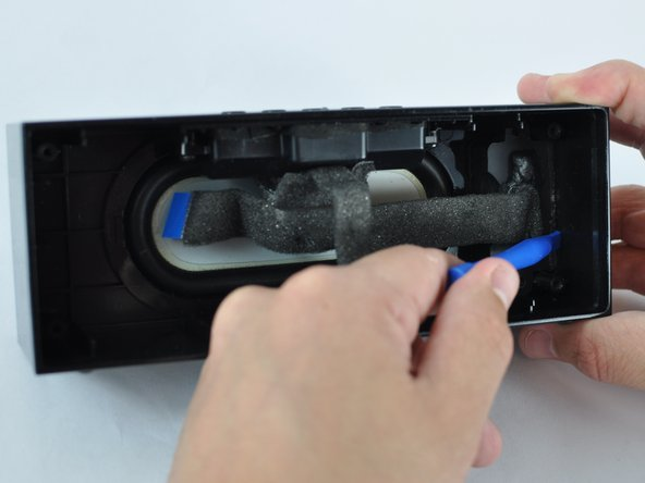 Use the plastic opening tool and tweezers at different points to work the audio input casing off.