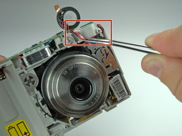 Pull the wiring at the top right of the camera away from the lens with tweezers.