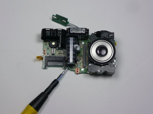 Locate the flash unit of the camera.  It includes the camera's flash and a capacitor.