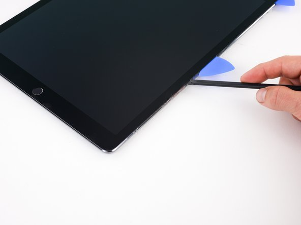 Image 1/2: Slide the halberd spudger down the side of the iPad to separate the adhesive.