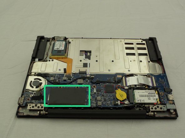 Locate the RAM under a black flap alongside where the laptop screen and device body meet.