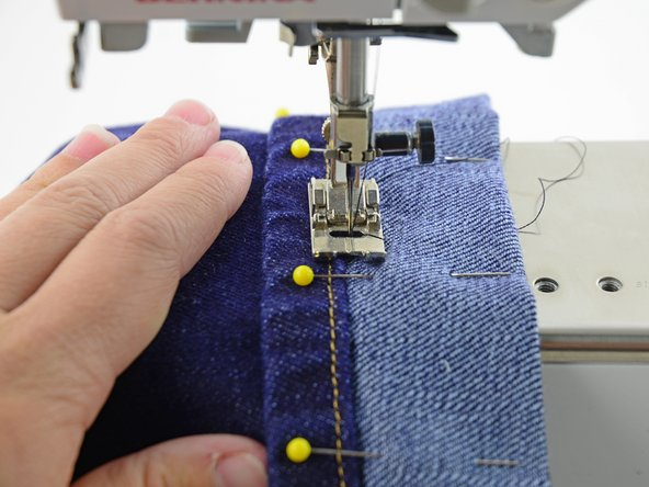Image 2/3: Lower the presser foot and take a few stitches, keep the line of stitches right at the edge of the hem.