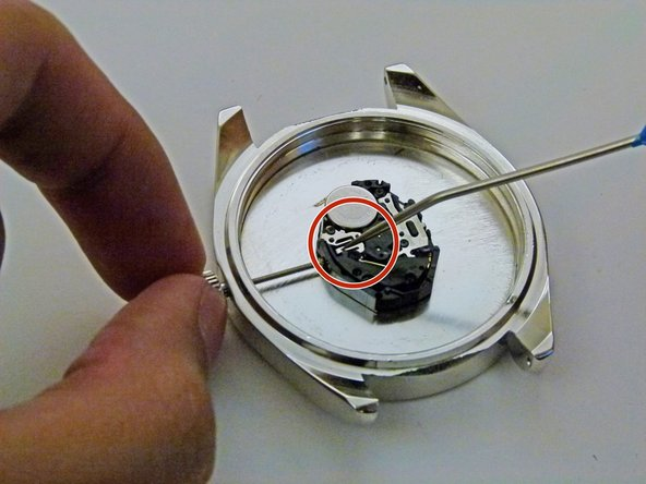 Apply pressure with the pointed tip instrument at the spot circled; around where the stem meets the main part of the watch.