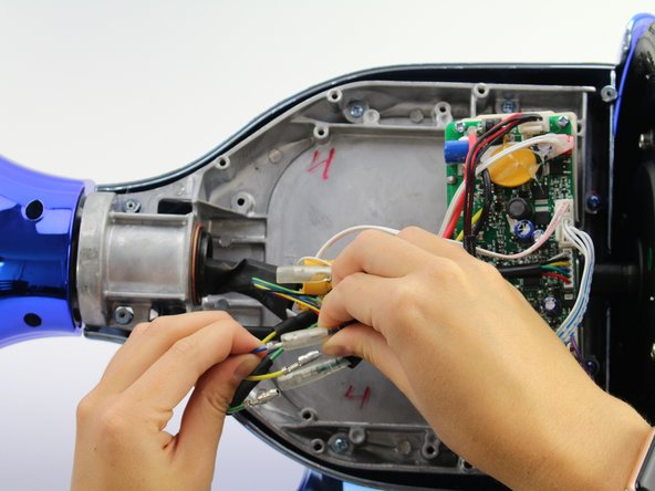 Unplug the blue wires by gripping the wire close to the connectors and pulling apart.