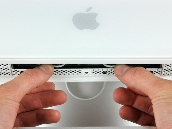Use your thumbs to press both RAM arms in past the front bezel for enough clearance to lift it off the rear case.