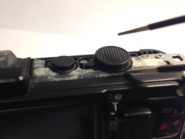 Image 2/3: Atop the camera, there are two buttons. The shutter button should be the largest of the two.