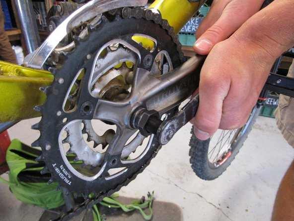 Image 1/3: The crank puller works by locking into the threads on the arm and pushing against the Isis drive axle to pry the arm and gears off. Make sure you are using the correct size crank puller, otherwise this step will not work.