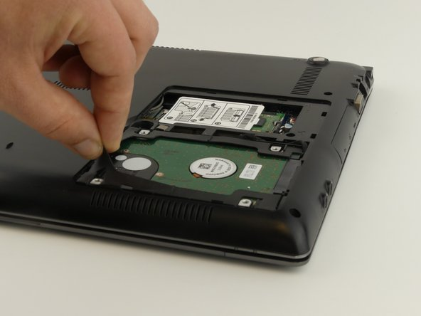 Image 1/1: Pull up on the rubber flap or use the spudger to lift the hard drive.
