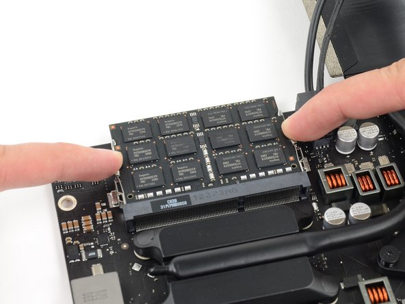 Image 2/3: Grab the top left and right corners of the RAM module and carefully pull it straight out of its socket.