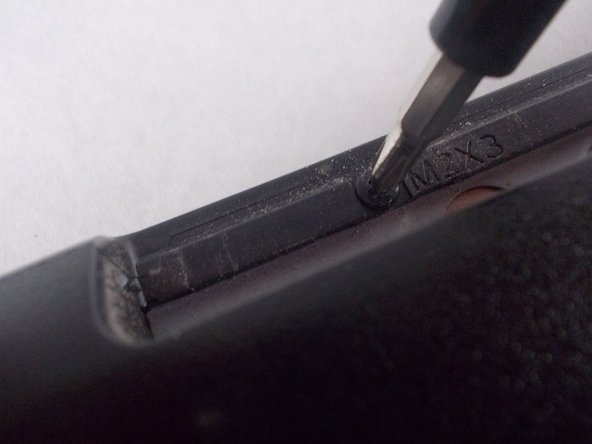 Unscrew the two 2x3 mm screws inside the disk drive compartment.