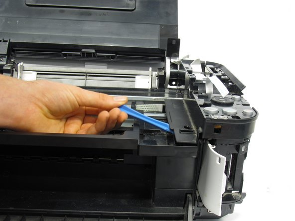Use the plastic opening tool to pry off the plastic button assembly.